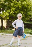 Beautiful little girl seven years old with pigtails in a school uniform. Outdoors stock photo