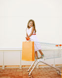 Beautiful little girl in shopping cart. With shopping bag Stock Images