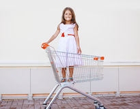 Beautiful little girl in shopping cart having fun outdoors Royalty Free Stock Photo
