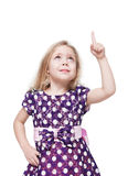Beautiful little girl showing on something by finger isolated Stock Image