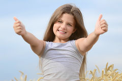 Beautiful little girl showing thumbs up on blue sky background. Concept of growth, happiness. All OK Stock Photos