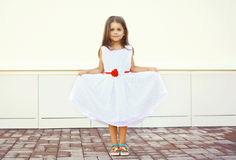 Beautiful little girl shows white dress outdoors Royalty Free Stock Photos