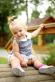 Beautiful little girl siting on the bridge Royalty Free Stock Images