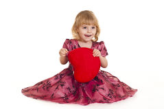 Beautiful little girl sits in a pink dress Stock Photos