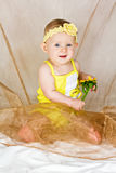 Beautiful little girl sits with yellow flower Royalty Free Stock Photography