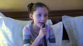 Beautiful little girl sitting on the bed in the hotel and watching TV. In the hands of a girl holding a remote control. Beautiful little girl sitting on the bed stock video