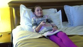 Beautiful little girl sitting on the bed in the hotel and watching TV. In the hands of a girl holding a remote control. Beautiful little girl sitting on the bed stock footage