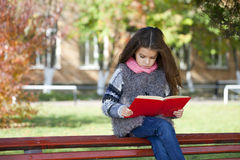 Beautiful little girl sitting on a bench Stock Photo