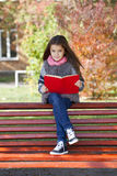 Beautiful little girl sitting on a bench Stock Photos