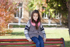 Beautiful little girl sitting on a bench Royalty Free Stock Photography