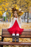 Beautiful little girl sitting on a bench Stock Images