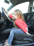 Beautiful little girl is sitting in the car Royalty Free Stock Image