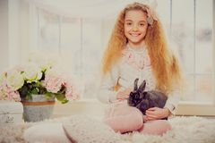 Beautiful little girl sitting on carpet and playing with bunny. Royalty Free Stock Photo