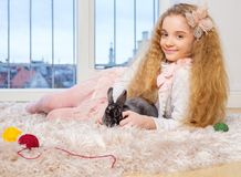 Beautiful little girl sitting on carpet and playing with bunny. Stock Image
