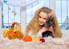 Beautiful little girl sitting on carpet and playing with bunny. Royalty Free Stock Image