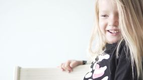Beautiful little girl is sitting on a chair and laughing stock video