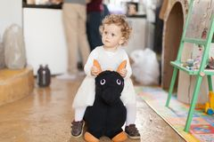 Beautiful little girl sitting on a donkey toy. Curly little girl sitting on a black donkey toy in a room with a easel to draw at home with people in the royalty free stock photo