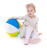 Beautiful little girl sitting on the floor and Royalty Free Stock Photos