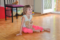 Beautiful little girl sitting on the floor and laughing Royalty Free Stock Photography