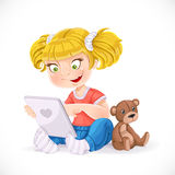 Beautiful little girl sitting on the floor with a tablet Royalty Free Stock Photography