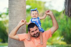 Beautiful little girl is sitting with her dad on her neck stock images