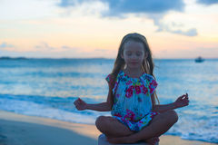 Beautiful little girl sitting in a lotus position Stock Photography