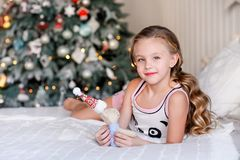 Beautiful little girl sitting near the Christmas tree. stock image