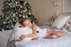Beautiful little girl sitting near the Christmas tree. royalty free stock images
