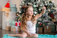 Beautiful little girl sitting near the Christmas tree. stock photo