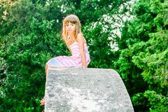 Beautiful little girl sitting on the stone structure. Beautiful seven year old girl is sitting on the top of the stone structure Royalty Free Stock Photo