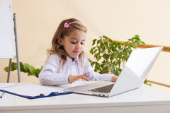 Beautiful little girl is sitting at table with laptop Stock Photos