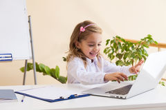 Beautiful little girl is sitting at table with laptop Royalty Free Stock Photography