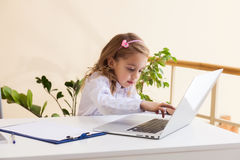 Beautiful little girl is sitting at table with laptop Royalty Free Stock Photos