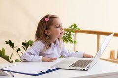 Beautiful little girl is sitting at table with laptop Stock Photography
