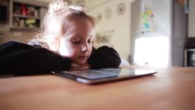 Beautiful little girl sitting at the table and watching cartoon on tablet computer,putting head on hands. Beautiful, cute little girl sitting at the wooden table stock footage