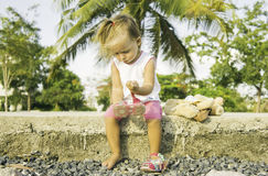 Beautiful little girl sitting on the waterfront and plays. Stock Image