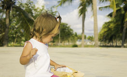 Beautiful little girl sitting on the waterfront and plays. Stock Photos