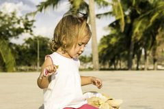 Beautiful little girl sitting on the waterfront and plays. Royalty Free Stock Photos