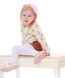 Beautiful little girl sitting on white banquettes Stock Photos