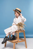 Beautiful little girl sitting white dress and straw boater holding wheat ears Stock Photos
