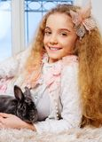 Beautiful little girl sitting on a windowsill and playing with bunny. Stock Images