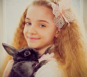 Beautiful little girl sitting on a windowsill and playing with bunny. Royalty Free Stock Photography