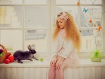 Beautiful little girl sitting on a windowsill and playing with bunny. Royalty Free Stock Photo
