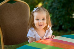 Beautiful little girl sitting on a wooden bench and have a cooki Royalty Free Stock Photo