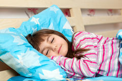 Beautiful little girl sleep in bed under a blue blanket. Beautiful little girl in pajamas sleep in bed under a blue blanket Stock Photo
