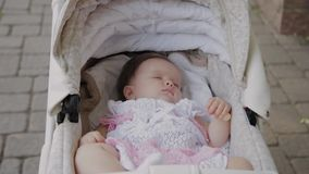 Beautiful little girl sleeping in a baby carriage on the street. Beautiful little girl sleeping in a baby carriage on the street stock footage