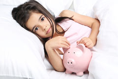 Little girl. Beautiful little girl sleeping with piggy bank in white bed Stock Image