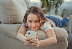 Beautiful little girl with smartphone. Leisure, children, technology and people concept. Leisure, children, technology and people concept - Beautiful little girl Royalty Free Stock Photos