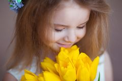 Beautiful little girl smelling the aroma of bouquet of fresh tulips. Spring and summer portrait of cute child holding. Flowers Royalty Free Stock Photography