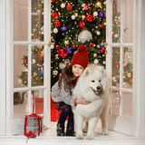 Beautiful little girl smiling and hugging a large white dog in C Royalty Free Stock Photos